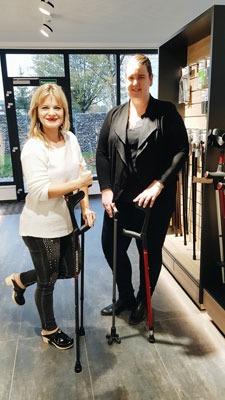 Schlagersängerin Sabrina Stern und Marketingleitung Jenny Sangaré posieren mit den Krücken der Ossenberg GmbH in dem Showroom von Ossenberg