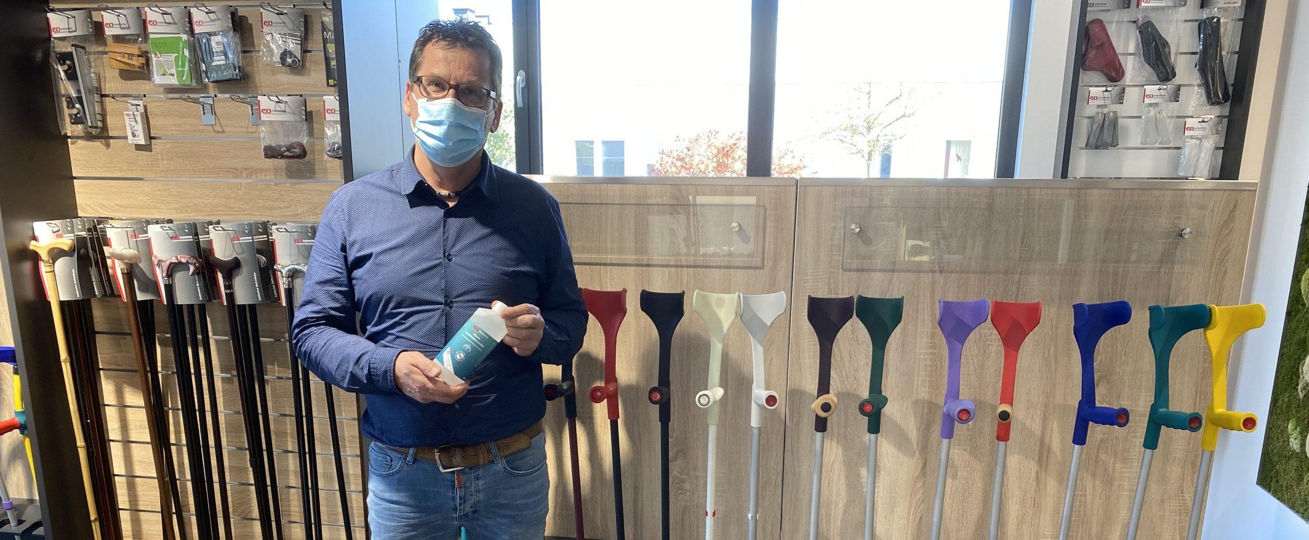 Geschäftsführer Carsten Diekmann mit Mundschutz und Desinfektionsmittel posiert vor Gehhilfen.